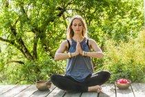 Mujer practicando yoga en terraza de madera - foto de stock