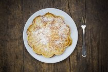 Waffles sprinkled with icing sugar on dark wood — Stock Photo
