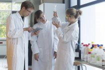Three chemists working in a chemical laboratory, one with test tube, another using digital tablet — Stock Photo