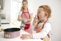 Mère et petite fille font du gâteau ensemble dans leur cuisine — Photo de stock