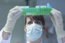 Jeune femme scientifique naturelle avec masque et gants de protection travaillant en laboratoire — Photo de stock