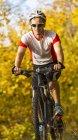 Человек на горном велосипеде в осеннем лесу — стоковое фото