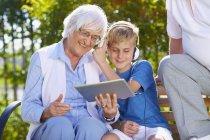 Внук, бабушка и дедушка с помощью цифрового планшета в парке — стоковое фото