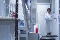 Biologo femmina in un laboratorio, che guarda l'obbiettivo con le mani incrociate — Foto stock