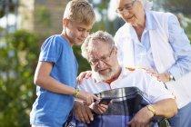 Бабуся і онук, пояснюючи стільниковий телефон, Дід в інвалідному візку — стокове фото