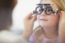 Eye doctor examining girl eyes — Stock Photo