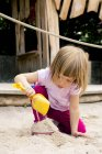 Little girl on playground balancing in sandbox — Stock Photo