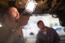 Two car mechanics at work in repair garage — Stock Photo