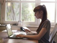 Жінка на реєстрації за допомогою ноутбука і їсть мюслі — стокове фото