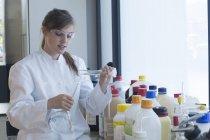 Молодые девушки химик, заполняя жидкости в получателя в химической лаборатории — стоковое фото