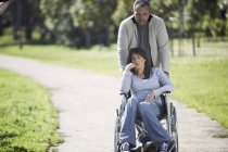 Man pushing woman in wheelchair in park — Stock Photo