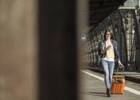 Femme avec bagages à pied à la gare — Photo de stock