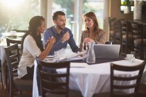 Business meeting of three people in a restaurant — Stock Photo