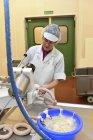 Frau, die arbeitet bei der Wurstherstellung in einer Metzgerei — Stockfoto