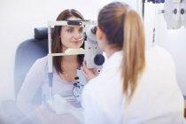 Eye doctor examining woman vision — Stock Photo