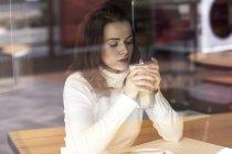 Junge Frau mit Latte Macchiato sitzt in einem Café — Stockfoto