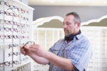 Man at the optician choosing glasses — Stock Photo