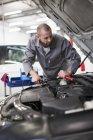 Car mechanic at work in repair garage — Stock Photo