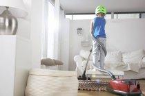 Мальчик в гостиной запутался в пылесосе — стоковое фото