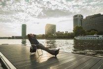 Deutschland, Frankfurt, entspannte Geschäftsmann am Mainufer — Stockfoto