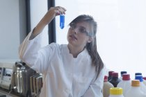 Young female chemist looking at reagent in a chemical laboratory — Stock Photo