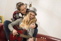Zwei Freundinnen spielen zu Hause zusammen Gitarre — Stockfoto