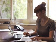 Frau am Schreibtisch mit Laptop-Seitenansicht — Stockfoto