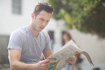 Retrato de hombre joven leyendo periódico - foto de stock