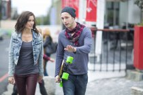 Young couple walking in the city, man holding longboard — Stock Photo