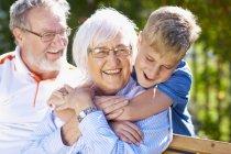 Улыбающийся внук обнимает бабушку в парке — стоковое фото