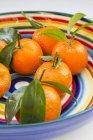 Mandarini freschi con i fogli in ciotola colorata — Foto stock