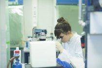 Femme scientifique naturelle regardant à travers le microscope en laboratoire — Photo de stock