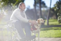 Smiling Man in wheelchair with dog in park — Stock Photo