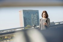 Germany, Frankfurt, young businesswoman on bridge with cell phone — Stock Photo