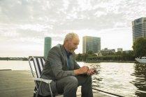 Uomo d'affari di Germania, Francoforte sul meno, usando il cellulare al fiume Main — Foto stock