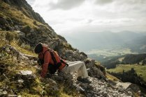 Austria, Tyrol, Tannheimer Tal, young female hiker having a rest in mountains — Stock Photo