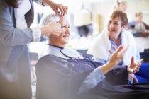 Parrucchiere femminile che taglia capelli di donna più anziana — Foto stock