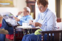 Senior woman knitting with husband in background reading newspaper — Stock Photo