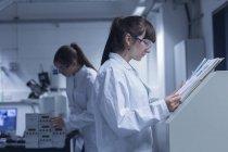 Dos técnicas femeninas que trabajan en un laboratorio técnico - foto de stock