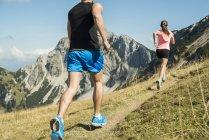 Autriche, jeune couple de Tyrol, vallée de Tannheim, jogging dans les montagnes — Photo de stock