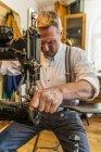 Saddler sewing vaulting belt at leather sewing machine — Stock Photo
