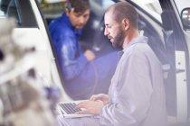 Deux mécaniciens de voiture avec ordinateur portable dans le garage de réparation en voiture — Photo de stock