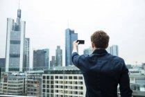 Германия, Гессен, Франкфурт, молодой человек, принимая картину skyline с его смартфон — стоковое фото