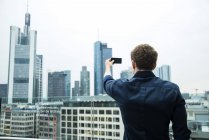 Germany, Hesse, Frankfurt, young man taking a picture of the skyline with his smartphone — Stock Photo
