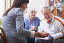 Mature Woman explaining document to senior couple — Stock Photo