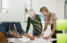Três jovens arquitetos em moderno escritório discutir — Fotografia de Stock