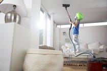 Мальчик в гостиной пылесосит потолок — стоковое фото
