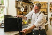 Saddler adjusting straps for leather rucksack — Stock Photo