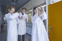 Trois chimistes travaillant dans un laboratoire de chimie font des tests — Photo de stock