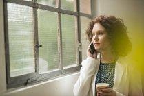 Молодий підприємець на мобільний телефон дивиться з вікна — стокове фото